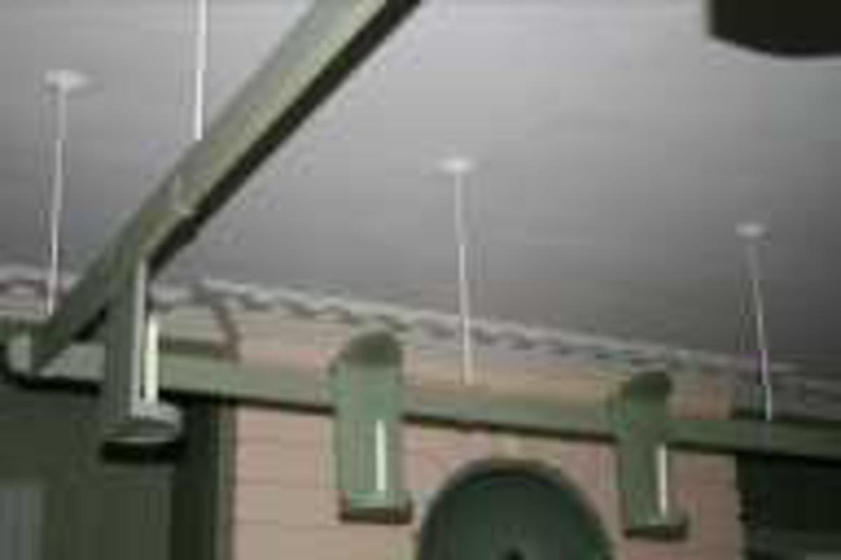 Treramme montert i taket. 10 lysholdere i blikk henger på ramma. Alt er grønnmalt.