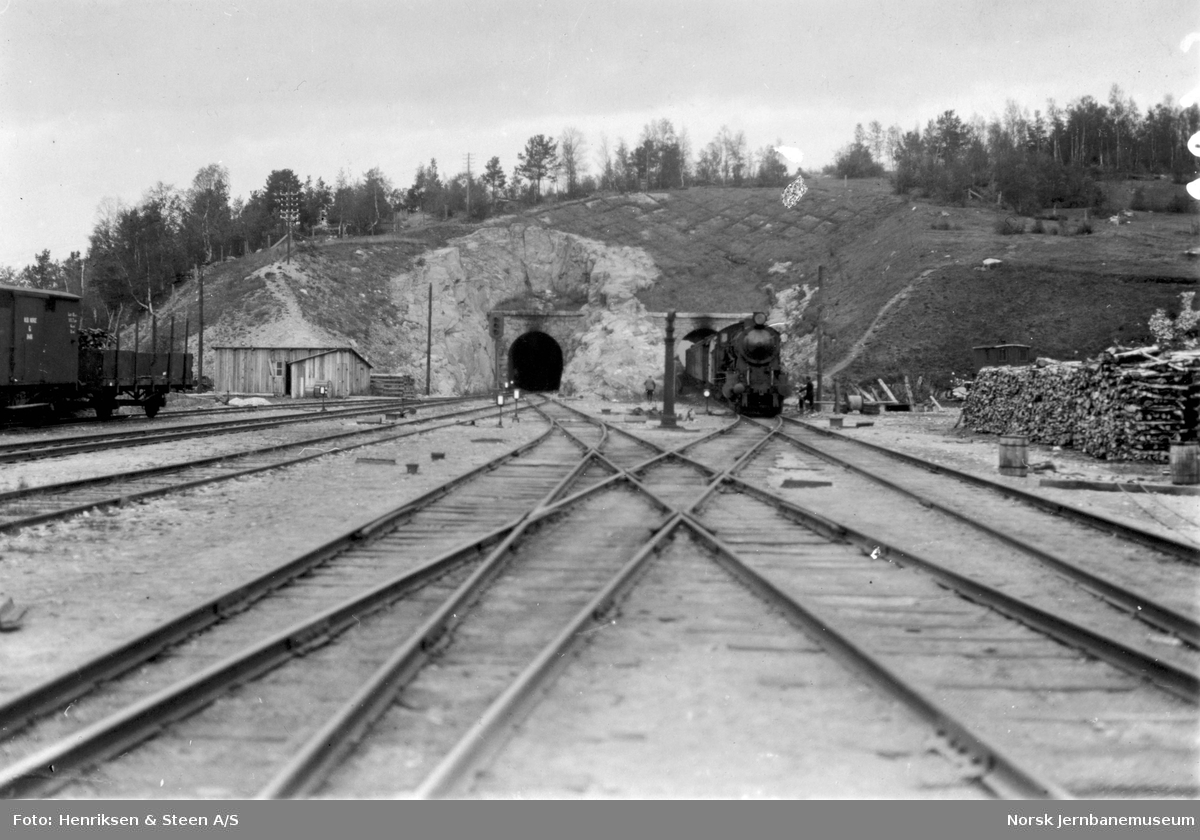 Dombås stasjon med tunnelene og ankommende tog fra Dovrebanen
