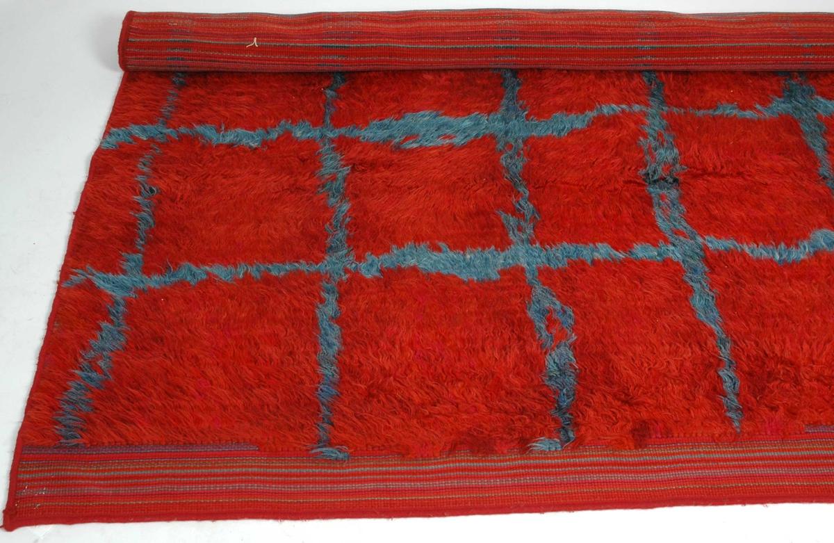 Rødt flosseteppe med turkois/grønn-blå striper i rutenett.  Broderte initialer: HK- Hjørdis Knutsen (designer).  KR og AT - trolig veverne. Nummerlapp fra vakeri festet med metallstift ble fjernet (28.08.06).