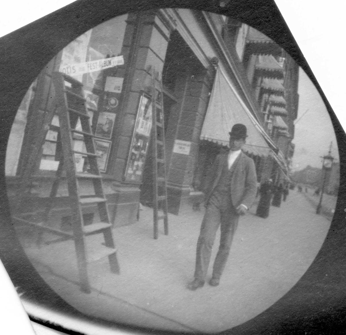 Thorvald Astrup spaserer på fortau langs butikker, Oslo. Markiser over vinduene, gardintrapp og stige mot vegg og vindu.