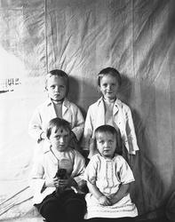 Portrett av fire barn, fotografert mot opphengt bakteppe, uk