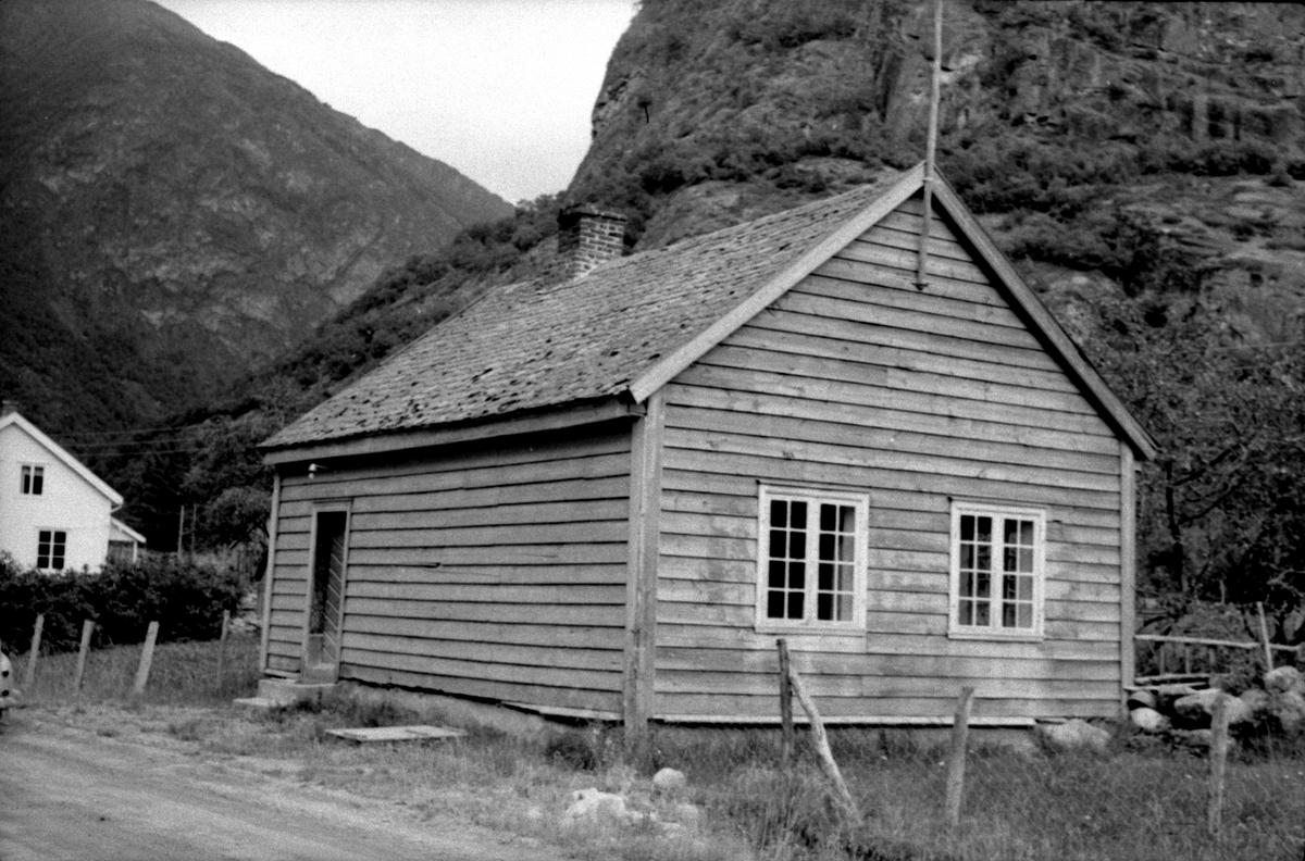 Ljøsne, Lærdal, Sogn og Fjordane, bygget 1866. Lite grått skolehus ved vei og mot fjell.. Registrering utført 1958-59 av Johan Schiong for Noregs Lærarlag.