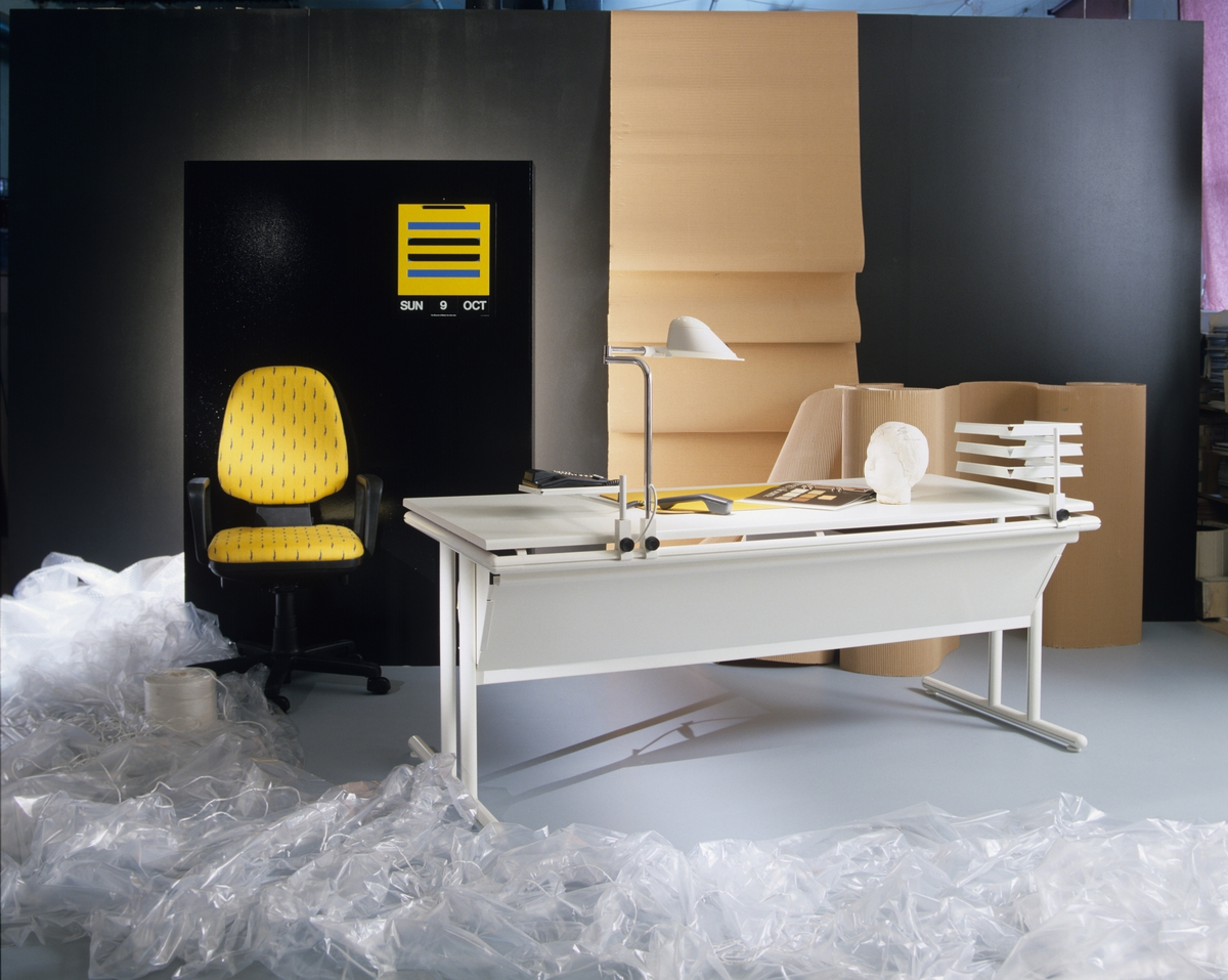 """Hjemmekontoret kalt """"Det smarte kontoret"""", hvor spesielle beslag gjør at du kan feste diverse utstyr til skrivebordet, skjule ledninger etc.  Stolen har en meget god ergonometrisk utforming. Illustrasjonsbilde fra Nye Bonytt 1988."""