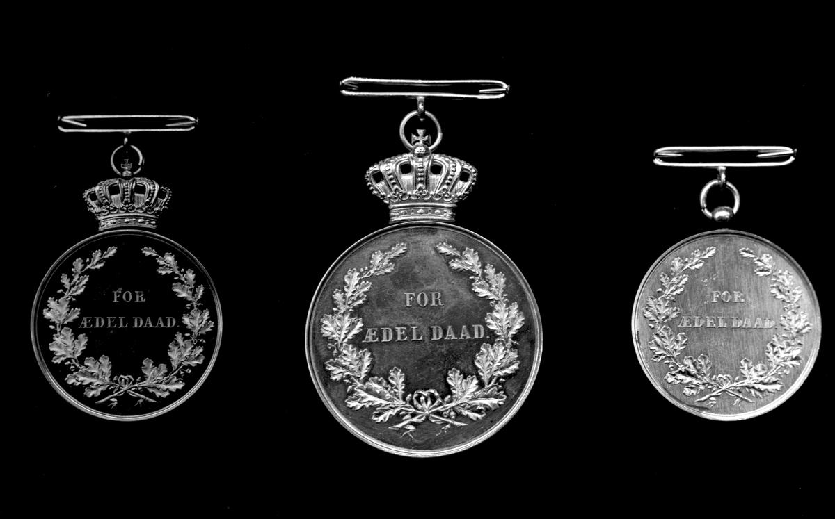 """Tre medaljestørrelser av """"For ædel daad"""", Oscar II Sverige og Norges konge. Baksidene, med løv og innskrift.."""