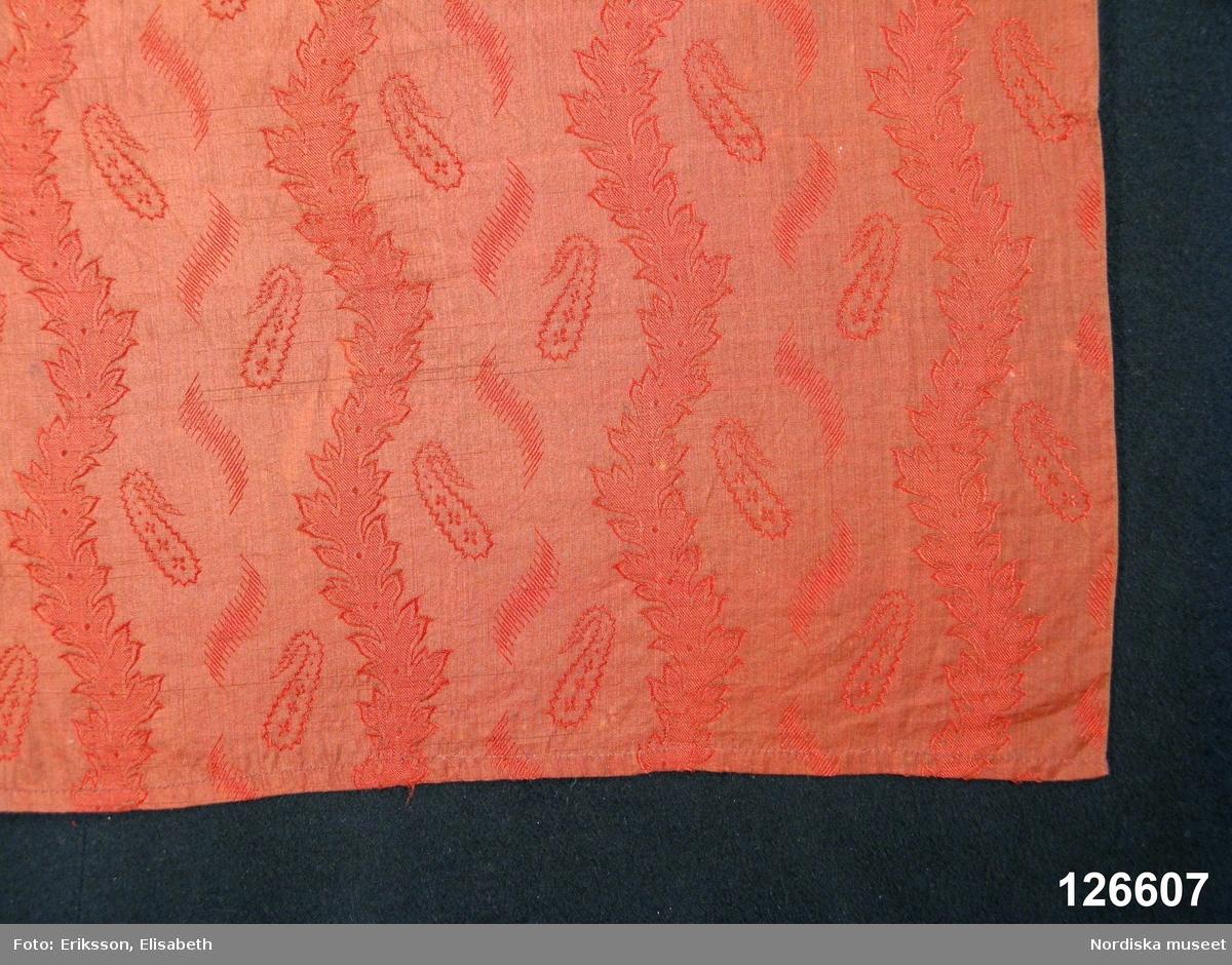 Förkläde av tunt mönstrat halvsiden. Varpen av tunt ljusbrunt bomullsgarn, inslaget av orangerött silke, botten i tuskaft med jacquardvävt mönster med bladslingor och mellan dessa små miribotafigurer och streckfigurer.Tyget är bara 50 cm brett och har därför sytts ihop på mitten av 2 våder, i midjan lagda veck mot 12 mm bred linning med fastsydda knytband av bruna bomullsband. Högra sidan har ett längre band avsett att knytas i vänster sida. Smal fåll i nederkant. I gott skick. /Berit Eldvik 2008-11-06