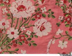 Söndersprättade delar till en ofullständig klänning. Tyget en sidenbrokad på stark rödrosa ripsbotten med blombuketter i vitt, mörkrött, rosa, och 2 gröna nyanser och slingrande vågband i vitt med mörklila prickar.  a.- b. höger och vänster framstycke med isydda korta ärmar. Flera skarvade bitar. 10 par snörhål i framkant, foder av oblekt linnelärft, i ärmarna vitt linne. c:1-c:2 2 avlånga bitar som varit hopsydda på mitten. I var ände sitter delar till livets bakstycken. Märken efter breda lagda veck längs ena kanten. På båda delarna fuktränder och blekning där de varit hopsydda.  d-e. svängda stycken med en rynkad sida. f- i  4 bitar av ärmarnas engageanter.  Tyget som är från 1760-70-talet verkar ha återbrukats flera gånger, möjligen inte bara som klänning utan även som möbelklädsel ( de smutsiga och blekta delarna kan tyda på det.) /Berit Eldvik 2008-12-19