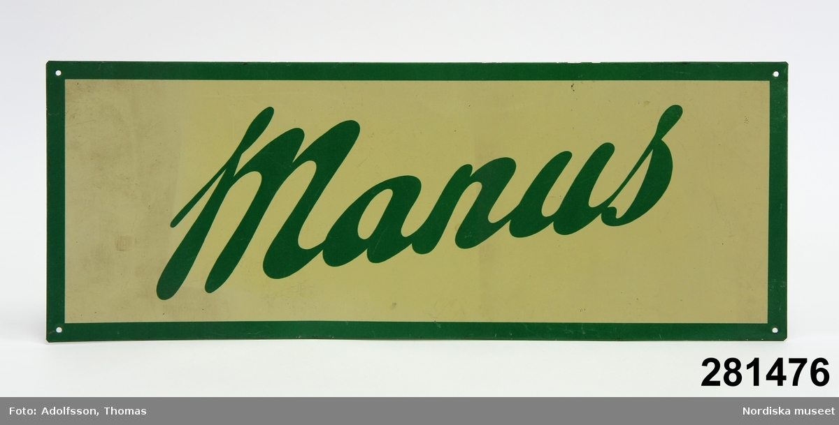 """Rektangulär reklamskylt för mjölkningsmaskinen """"Manus"""" tillverkad i Norrköping. Med grön kant och mot vitgrön bakgrund är ordet """"Manus"""" skrivet i grönt. Med 4 hål för montering.   ULHA 2008-03-31"""