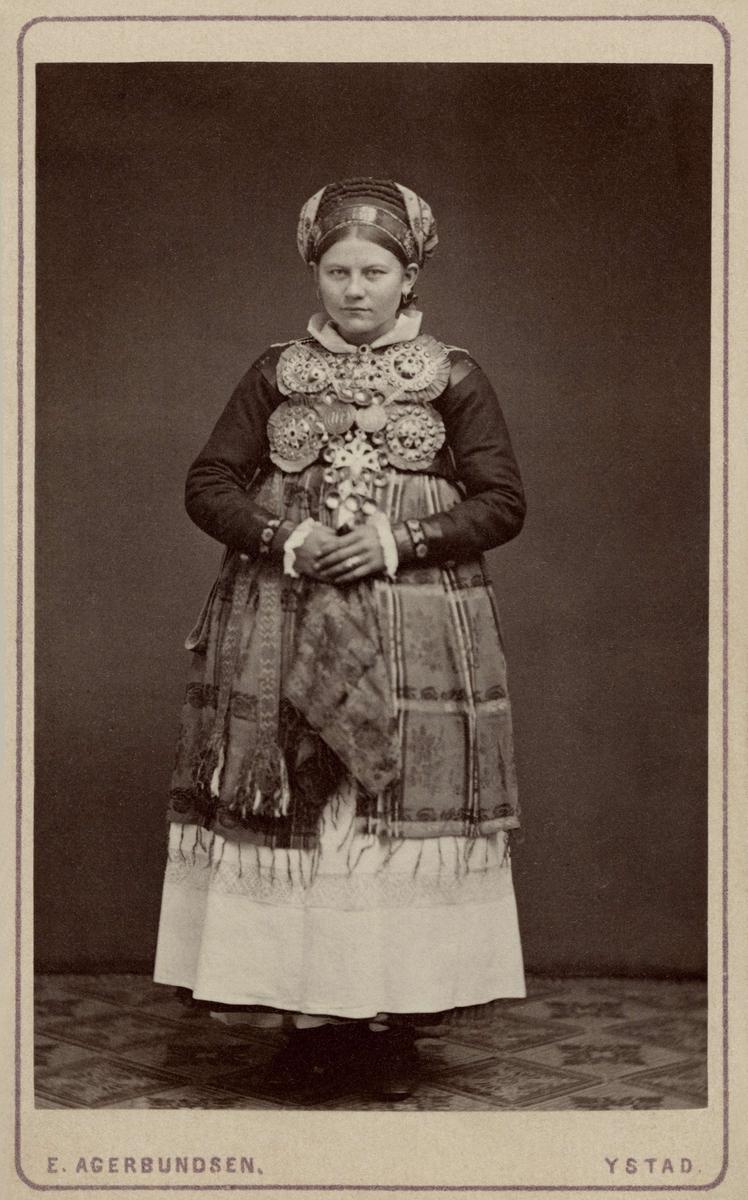 Porträtt av stående kvinna iklädd folkdräkt. På kortet är noterat att hon bär bruddräkt från Ingelstads härad i Skåne. Nordiska museet inv.nr. 18541C