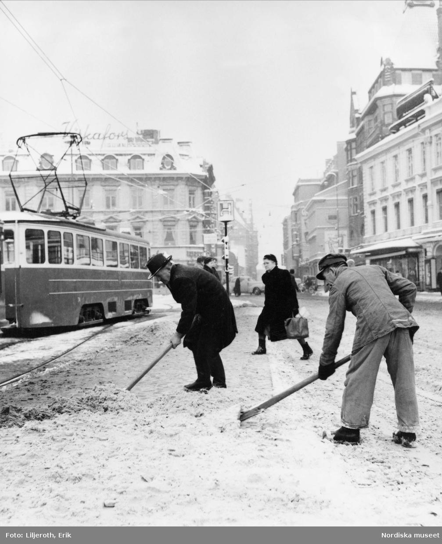 Två män skottar snö i Malmö centrum