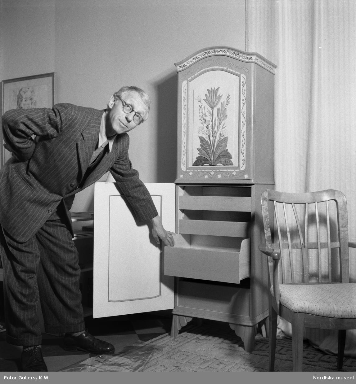 Professor Carl Malmsten, möbelformgivare och inredningsarkitekt, drar ut låda i skåp i allmogestil.