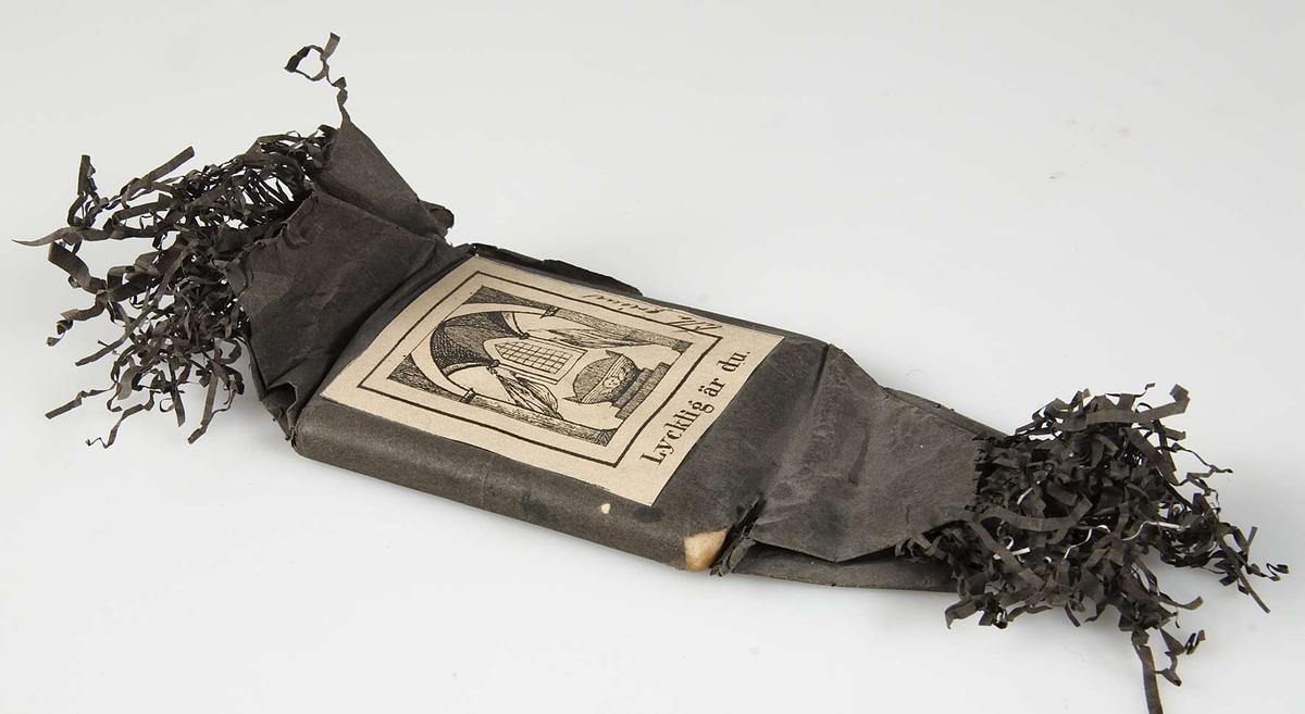 """Begravningskaramell, svart silkepapper. Svartvitt märke med likkistmotiv med text: """"Lycklig du är""""."""