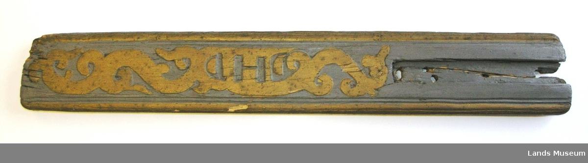 Mangletre som mangler håndtak. Dekorert med enkel ranke som  i midten danner initialene DHD.