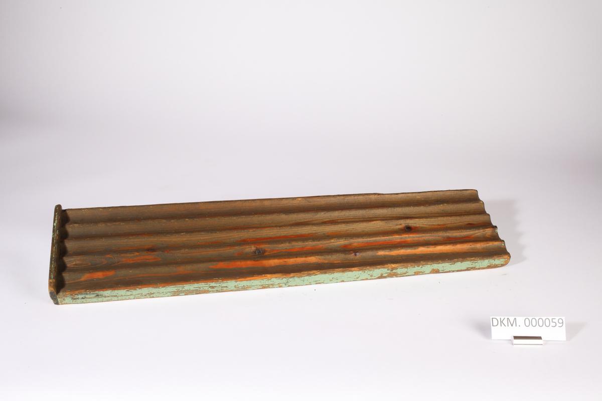 Avlang planke med fem langsgående riller. Rillene er åpne i den ene enden og stengt i den andre enden.