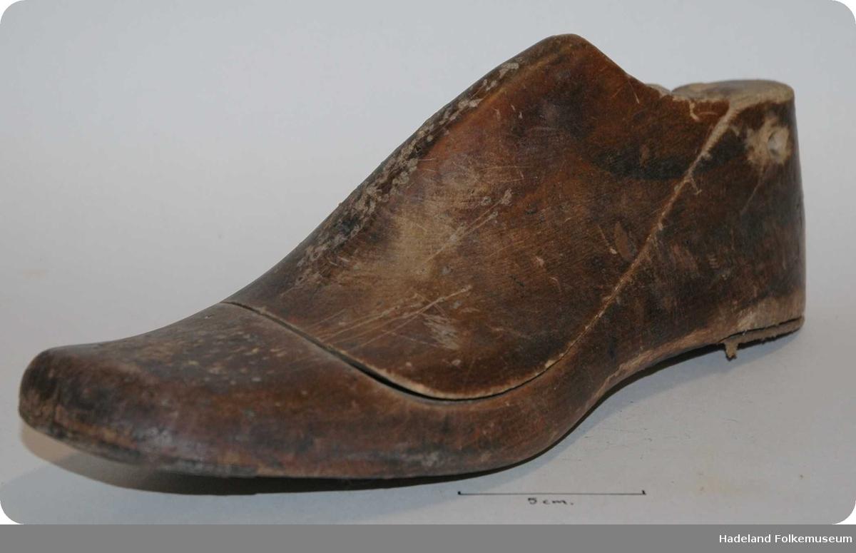 Skomakerredskap. Form til å sy sko over. Tre, skåret. Grovt formet som en fot.  merker etter stifter/plugger. 2 deler.hullet 2 steder.Lærlapp hæl + tå.