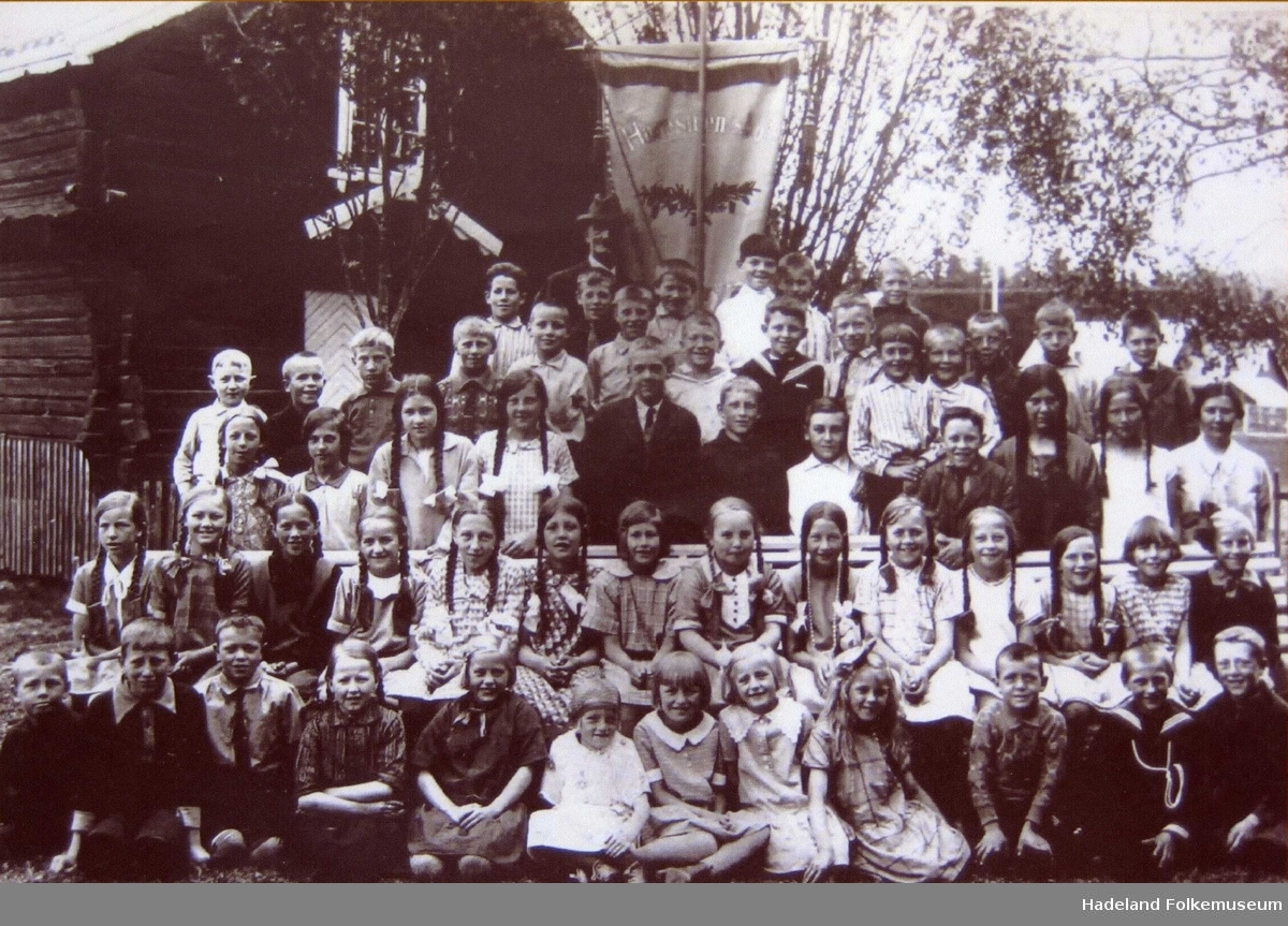 Klassebilde 1. klasse Harestua skole ca 1925 ved stabbur med fane i bakgrunnen.