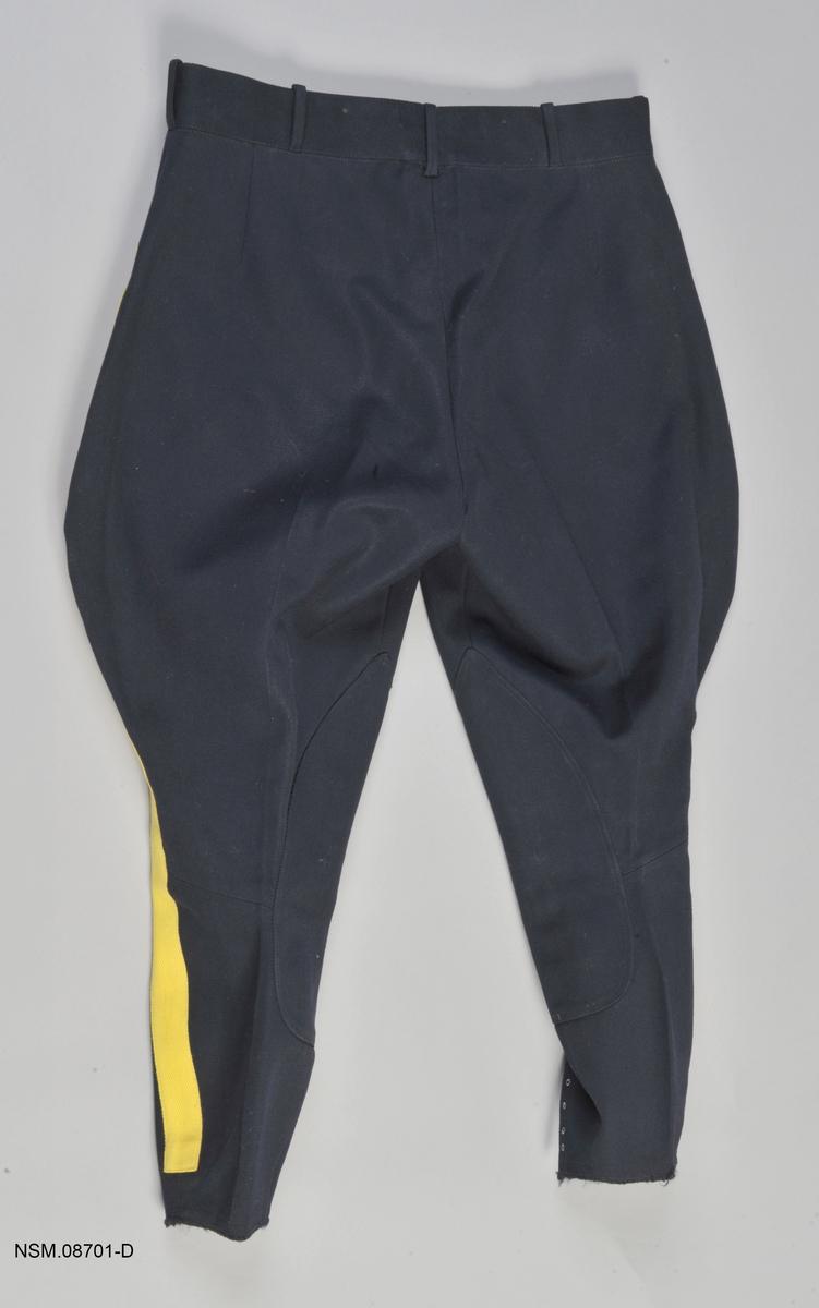 Ridebukse, blå med gule striper på bena. For Royal Canadian Mounted Police.