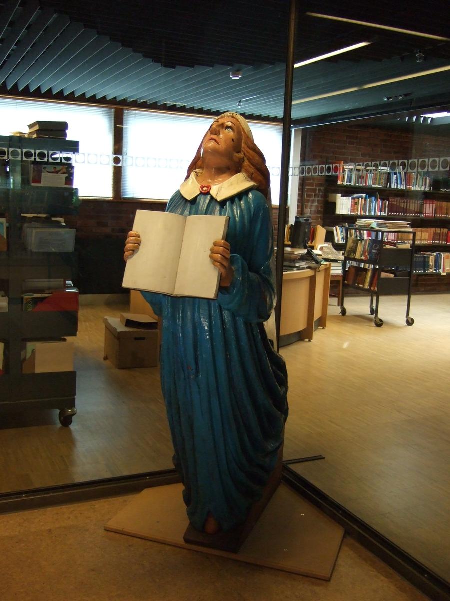 Kvinnefigur, foroverlent, holder en åpen bok i hendene. Blå kjole, gulbrun hudfarge, grå sokkel.
