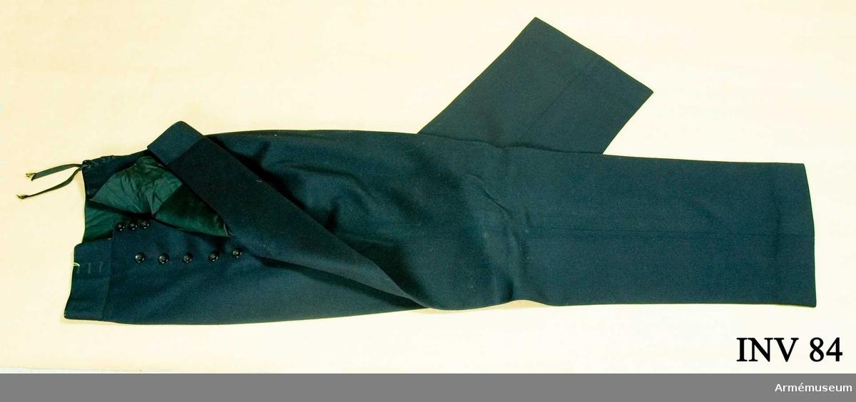 Av mörkblått kläde. Fodrad i livet med svart siden. Två sidofickor. Snörning bak. Tolv bakelitknappar i gylfen. Har tillhört Gustav VI Adolf (1882-1973).