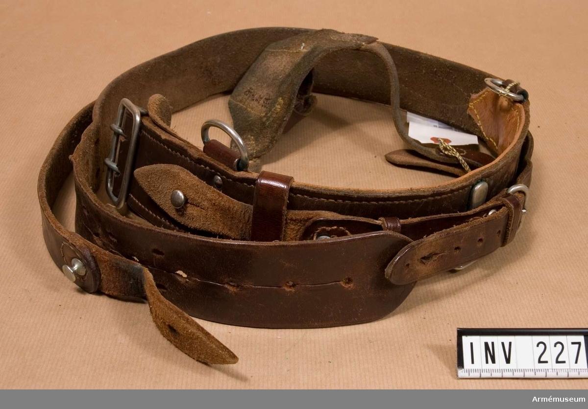 Samhörande nr är 209-238 (220-238). Livrem med axelrem m/1923. Av brunt läder. Spänne och metalldelar av vitmetall. Remmen spännes genom ett kraftigt spänne (60 x 40 mm) med två taggar, fasthålles i sitt läge med sölja och kraftig knapp på hals, lädrets tjocklek. En kraftig krok och oval ring för bajonettens fasthållande, rektangelformade. Axelrem fäst vid livremmen i två ringar (raka vid livremmen) genom omtag mot framsidan och fasthållen med en knapp i metall på hals (hög som lädrets tjocklek). Remmen är ställbar med spänne och hål. Bäres av officer.