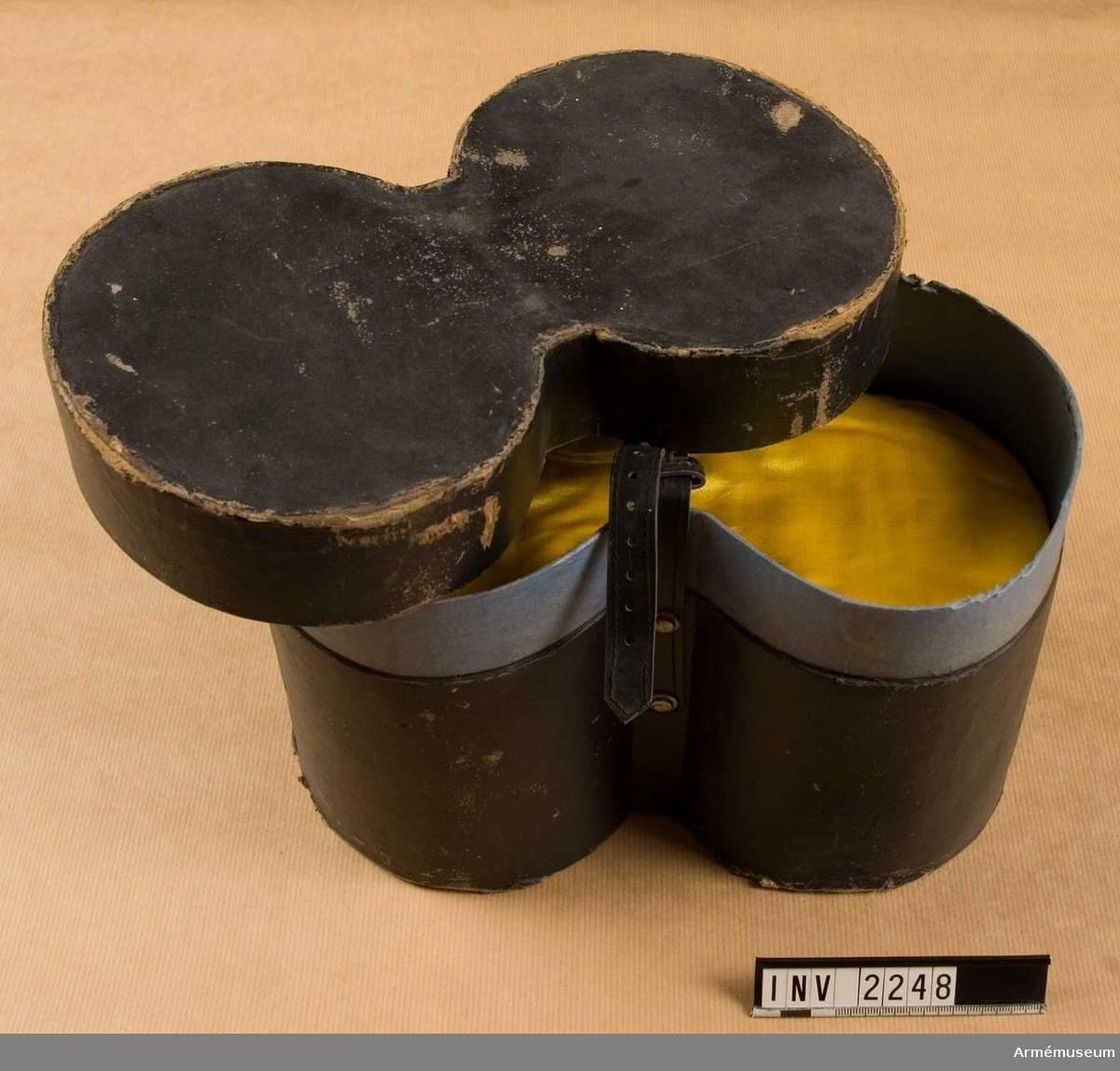 """Yttersidan svart. Foder av blå papp. Märkt i locket """"G J M  Fyrwald & Co"""". Formad för att passa till två epåletter liggade  med halsarna mot varandra. Asken stänges med läderrem. Två gula sidenkuddar stoppade med vadd hör till. I mitten av asken är ett stöd för epåletterna monterat så att fransarna kan hänga rakt."""