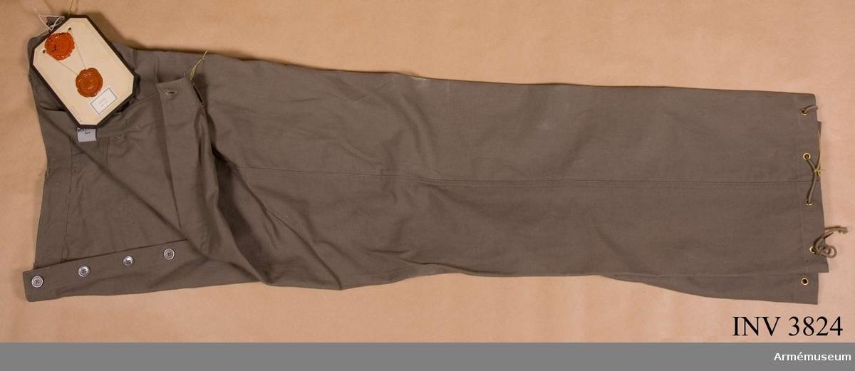 """Av gråbrungrön bomullstwills. Två halvsneda sidfickor, en  påstickad bakficka. Sex hällor f bälte. Spänntamp i ryggen f  reglering av livvidd. På linningen sex knappar f hängslen. I  uppvikningsfållarna åtta öljetter i vart byxben jämte byxsnören. Alla knappar av bly. Pga rådande förhållanden och därmed materialbrist, ersattes dessa knappar m i handeln förkommande. Märkt """"Slitman"""" på vävd etikett vid V yttersöm i linningen. Vidhängande etikett anger fastställelsedag: """"19. februari 1941"""". Undertecknat av Per EdvinSköld, chef FÖD, Henry Kellgren, chef  LKE."""