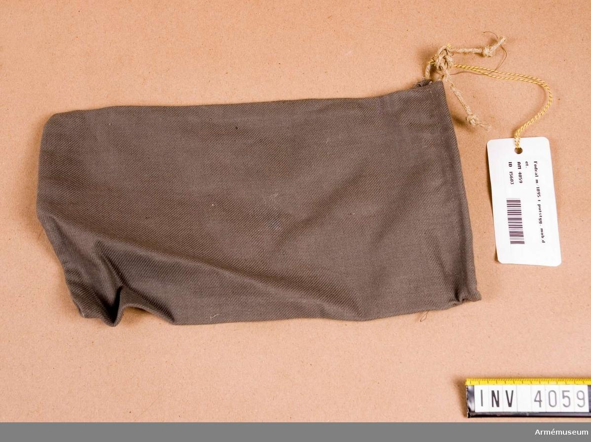 Fodral m/1895, t putstyg.Obegagnat skick. Mått: 275 x 160 mm. Fodral till putstyg m/1895, av gråbrungrönt kypertvävt tyg i bomull. Upptill en dragsko för band, i detta fall ett vanligt snöre (papperssnöre). Vändsöm i botten och på en sida. Fodralet  är på insidan delad i två fack genom en vägg av tyget. Har  tillhört Rustmästare Olle Skoogs mobutrustning.