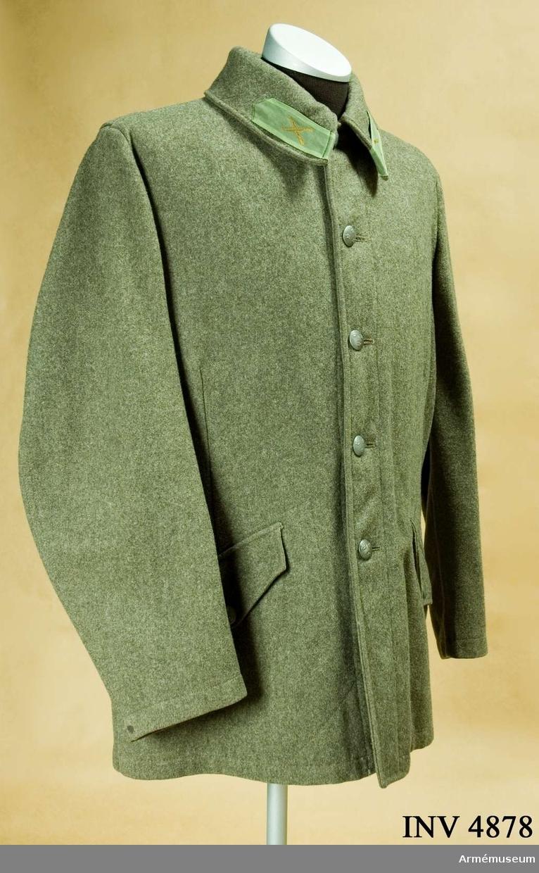 Storlek: 96. Vapenrock m/1958, menig, fältuniform I 1. Tillverkad av gråbrungrönt ylletyg, är enradig, högknäppt i halsen, har  grenslejf, två snedställda fickor, sid- och två bakfickor. UNIA 1977 6:101-112.