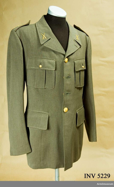 Storlek: 100. Av gråbrungrön yllediagonal med knappar och  truppslagtecken i mattförgyllt guld m/1952. Vapenrocken är av  m/1939 med utbytt emblem m/1952. På axelklaffarna HM Konungens namnchiffer G VI A m/1950-60 samt tre stjärnor = kapten och liten knapp I 1 m/1779. På kragsnibbarna truppslagstecken för  infanteriet, två korslagda musköter. Knapparna som är bottnade  är tillverkade hos Sporrong, Stockholm. På vänster sida i fodret en etikett: ÖRNKLÄDER. Gåva av kapten Thore Lindegård, f d I 1:s reserv.