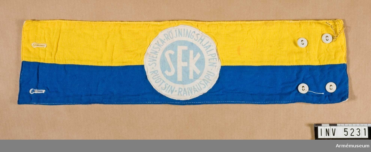 """Armbindel för """"Svenska röjningshjälpen för Finland"""". Armbindeln är hälften gul och hälften blå på längden. Mitt på sitter ett runt märke, blått och vitt med text. Bindeln knäppes under ärmen med två knappar. Den är fodrad med halvblekt domestik."""