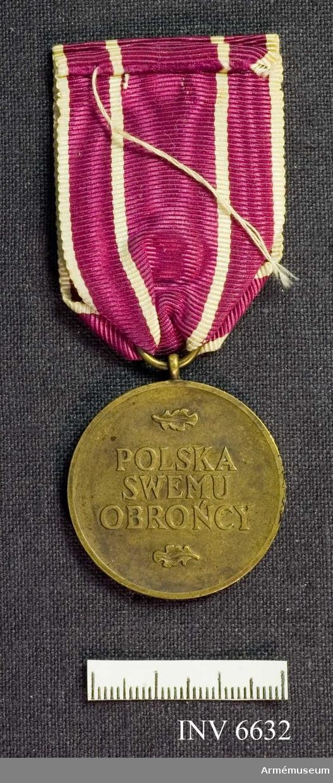Medalj, Polska Swemu Obroncy 1945.  Text på frånsidan och med den fläkta örnen på framsidan.   Samhörande lila ripsband med fyra smala vita ränder.