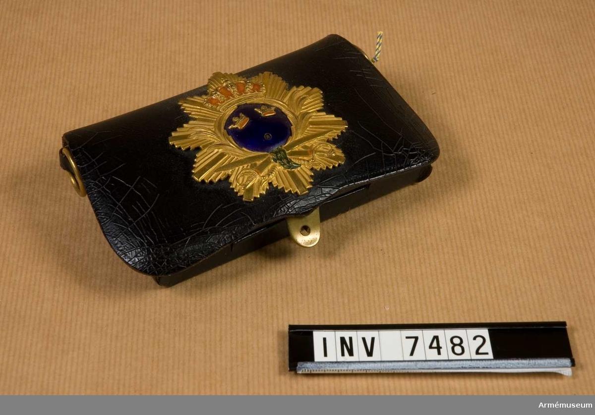 Låda av svart lack med inredning. Märke för officer vid SVEA, Andra Svea, senare Upplands artilleriregemente, Positionsartilleriregementet samt Norrbottens artillerikår. En krona saknas.Kartusch var i bruk som paradpersedel till 1931 (utom cheferna för A 3 och K 2). Märket upptar inom en strålkrans Svea rikes vapen (tre kronor). Se AM Meddelande 1977-78 Kartuschen en intressant relikt av Tore Karlsson.