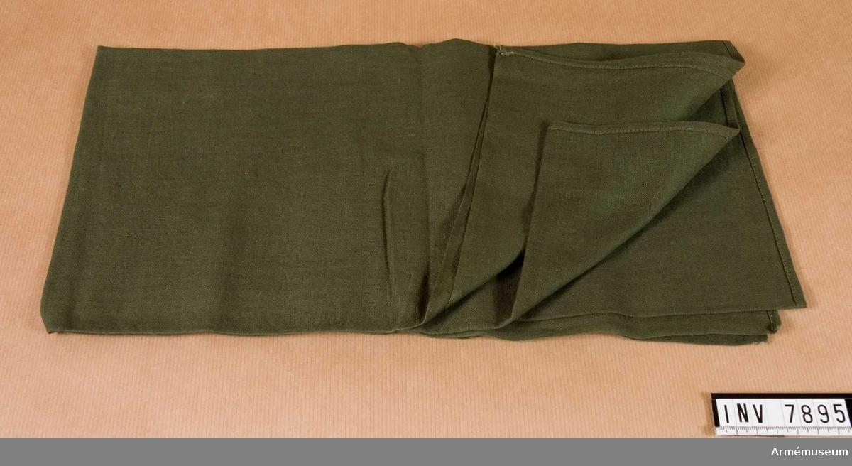 En fyrkantig halsduk sydd av tunt grönt bomullstyg.