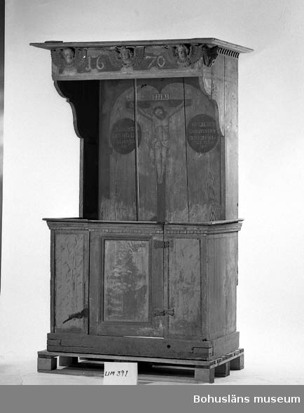 Målad skriftestol från 1670 med baldakin. Ursprungligen från den år 1876 rivna kyrkan i Brastad. Skriftestolen är tillverkad i massivt trä. Allt måleri är grunderat med en röd (förmodligen) limfärg. Måleriet är utfört i olja och på vissa parter sekundärt övermålat. Skriftestolen är krönt av fem snidade änglahuvuden, vilka ursprungligen varit sex. Motiv: bl. a. Kristi korsfästelse.  Ur handskrivna katalogen 1957-1958: Kyrkobänk, Brastad Bottenmått 112 x 76. H: 204. Skriftestol m. baldakin. Märkt 1670. Målad. Färgen delvis borta, Brastad k:a. 13  Lappkatalog:13