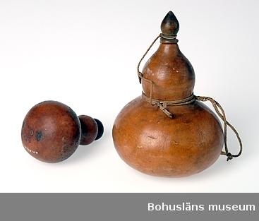 """Text till webbutställning """"Från när och fjärran"""" presenterad på Bohusläns museums hemsida år 2009 - 2013: Flaska av kalebass med propp av svarvat trä; höjd 15,5 cm. (Den vänstra flaskan är UM000833.) Sydafrika 1860-talet. Av det torkade fruktskalet från en gurkväxt, kalebasspumpa, har sedan århundraden gjorts flaskor, kärl och musikinstrument. Flaskkurbits, kalebass och kalabass är benämningar på samma frukt.  Uppgifter om givaren Skänkt av Stadsmäklare August Spaak, Göteborg år 1917. I en äldre handskriven katalog över museets samlingar står angivet om givaren som """"en av Uddevalla musei flitigaste gynnare"""".  Kontinent: Afrika Ur handskrivna katalogen 1957-1958: Kalebassflaska, Afrika Flaskan a) H. 12 cm, största D. 10,5 cm. Proppen b) L. 4,3 cm; av trä, Svarvad. Föremålen hela.  Ur Knut Adrian Anderssons katalog 1916: No 31 Kalebass-flaska 12 x 12 cm med träpropp; negerarbete 1860-talet från S. Afrika. Gåva 16/8 1917 av herr Aug. Spaak.  Stadsmäklare Aug. (August) Spaak, Göteborg; skänkt gåvor både på 1880-talet och 1917; afrikaföremål samt föremål hemförda från Söderhavsöarna 1856.  Korrespondentredare; den som sköter rederiverksamheten för ett fartyg utan att vara dess ägare. (Internet: Advokatfirman Ihre AB; register.) Stadsmäklare; i Sverige benämning på offentlig, af en stads handels- och sjöfartsnämnd auktoriserad mäklare, dock vanligen i den inskränktare betydelsen af sådan mäklare, som icke är fondmäklare. (Nordisk familjebok 1917)  Litteratur: Webe, Gösta, Nautika, Sjöhistorisk årsbok 1985-1986, s. 297-299."""