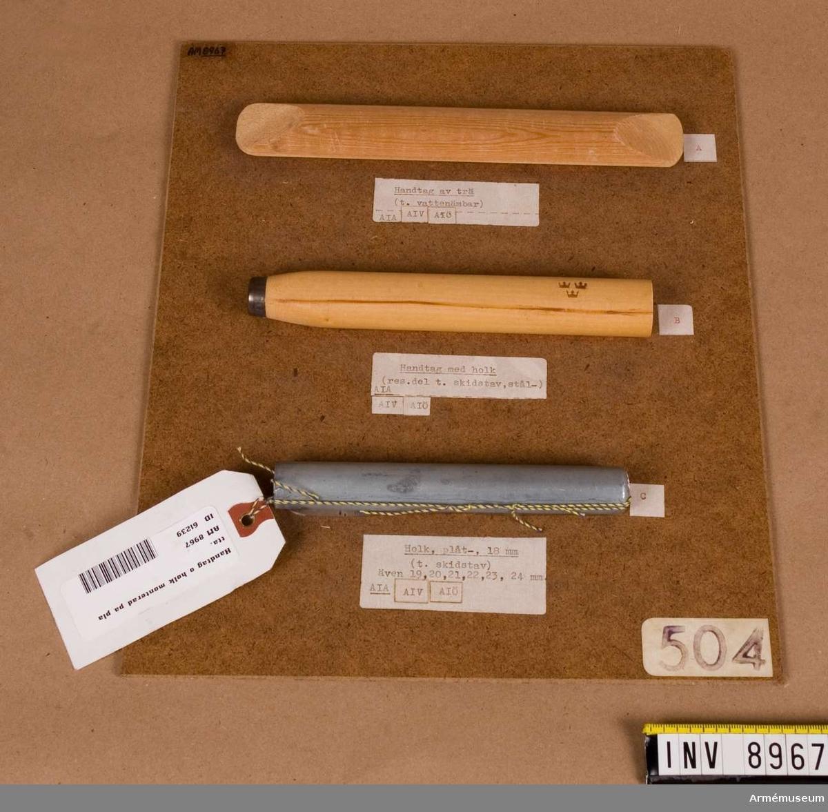 """Platta av """"masonite"""". Bestånde av fyra delar: 1 st platta av """"masonite"""", 1 st handtag av trä till vattenämbar (A), 1 st handtag med holk, reservdel till skidstav, stål (B); 1 st holk av plåt, 18 mm till skidstav."""