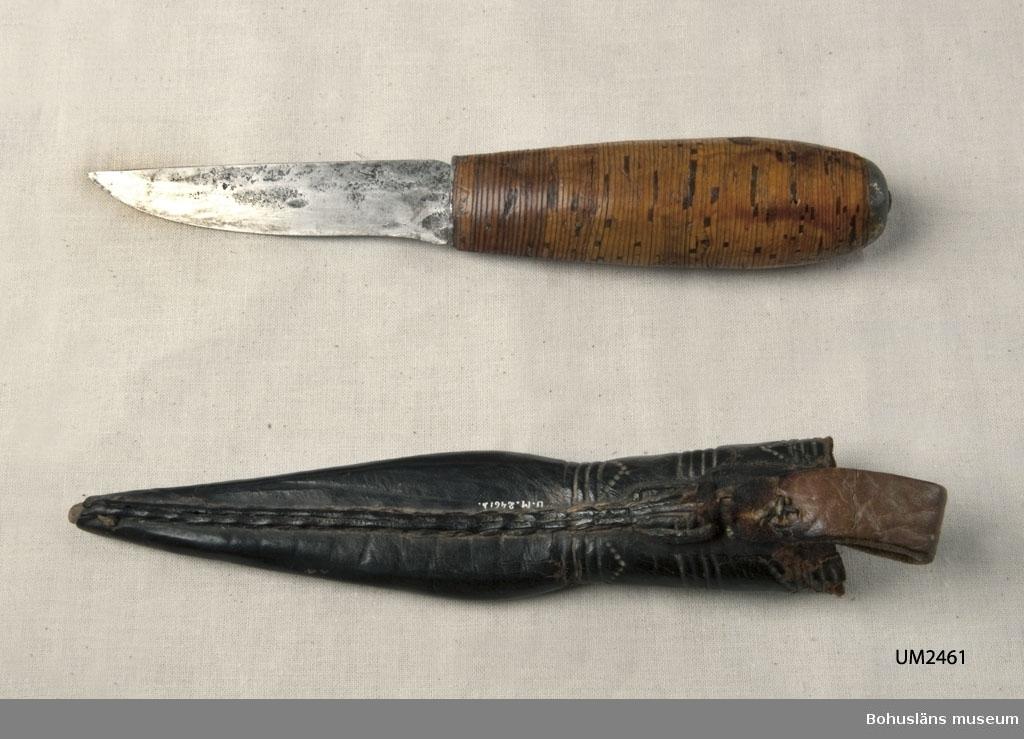 Knivens skaft är gjort av björknäver som packats tätt kring tången. Slida av svartfärgat läder med inpressad dekor. Upphängningsögla av läder. I bruksskick.  Ur handskrivna katalogen 1957-1958: Slidkniv m. näverskaft o läderslida Kniven a) L. 19,5 cm; skaft av näverplattor(?) m. beslag av plåt. Slidan b) L. 17 cm; av svart läder; trasig. Kniven hel.  Lappkatalog: 29