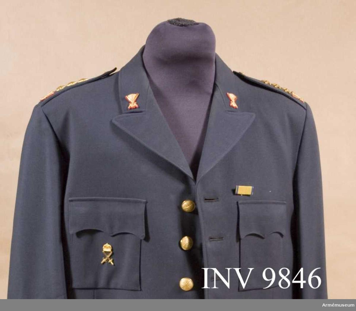 Av gult silke i rips med kanter i blått silke. På baksidan ett spänne. Sitter till vänster på bröstet av uniformen.