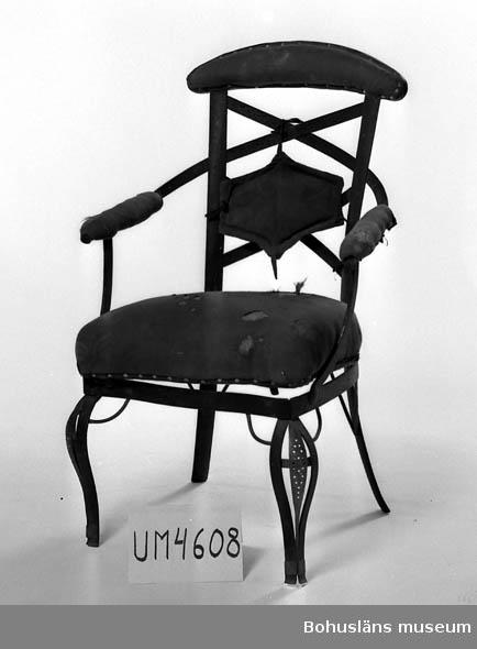 Ur handskrivna katalogen 1957-1958: Järnstol H. 93 Sitsen L. 47. Br. 44. Sitsen, armstöd o del av rygg grönklädd. Järnet grönmålat. Något illa medfaren.  Lappkatalog: 82