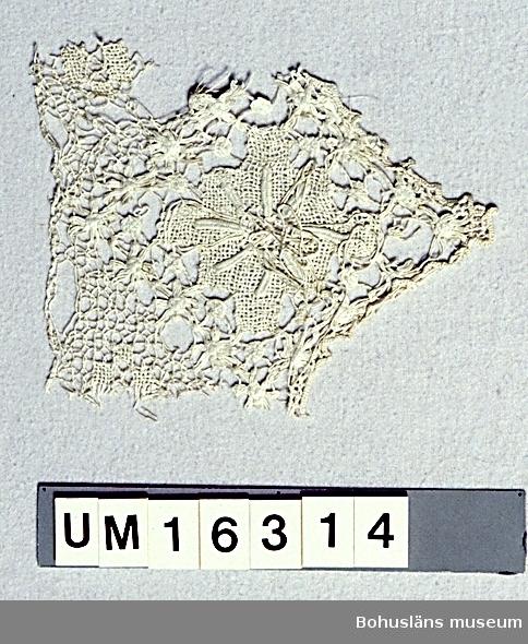 """471 Tillverkningstid 1910-TAL? 594 Landskap BOHUSLÄN  Filéspets-fragment av vitt lingarn . Trädda trådar i ett knutet nät med kvadratiska rutor, troligen inspirerat av knypplade spetsars  utseende. Mönstret består av en stor blomma med små cirklar och blommor runtomkring. Stora blommans glesa botten är gjord i dubbel trädsöm (dvs trädningar från två håll) och det övre skiktet som liknar knypplade """"spindlar"""" är sydda i stoppsöm. Cirklarna och de små blommorna är tätt trädda. Trekantig udd, kantad med langettstygn. Samma mönster som UM 16313. Uppgifter om givaren se UM 16300. Dateringen gjord utifrån att spetsen inte liknar de filéarbeten som gjordes i allmogemiljö under 1800-talet, därför är det troligare att den är från 1900-talets första decennium när filéspets blev populär. Några hål och hängande trådändar.  Litt; Melén, Lisa, Knutet och trätt, sid. 8. Widhja, Inger, Takhimlar och brudhandskar Folklig textiltradition i Västergötland, Skara 1990, sid. 78 -83.  Omkatalogiserat 1997-08-21 För ytterligare uppgifter om givaren se UM 16300."""