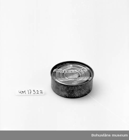 """Rund violett burk, gul textremsa: """"Sill i lök. A-B. Elis Luckeys Konservf. Lysekil inneh. 95 gr. kvalitetsvaror. Billigt sandelkryddad."""" Se UM17232."""