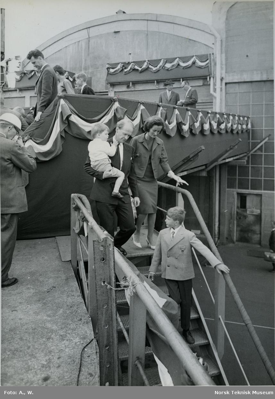 Fred. Olsen på vei ned fra tribunen sammen med to barn og en kvinne etter stabelavløpning av tankeren M/S Landvard, B/N 527 på Akers Mek. Verksted 14. juni 1962. Skipet ble levert i 1962 til Klosters Rederi.