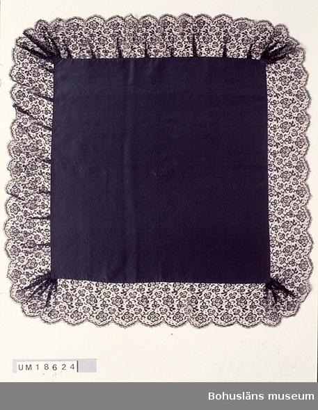 """Kvadratisk svart schalett av sidenrips. Med 13 cm bred maskintillverkad spets av silke, småmönstrad med blommor och blad, fastsydd för hand ytterst. Spetsen är lagd i veck vid hörnen och  längs två av sidorna,  men slät längs två sidor. Tillverkningstid enligt tidigare katalogisering 1900-tal. Schaletten  har tillhört Hilma Samuelsson, Ulebergshamn, f. 1862 d. 1923. Användes tillsammans med UM 18625 (paraply) och UM 18628 (kappa) som helg-, fest- och kyrkbesöksplagg. Ansågs mer påkostat än vad en stenhuggarhustru vanligen kunde kosta på sig. Se bilaga för uppgifter om släktskapsförhållande mellan brukare och  givare.  Liten vit fläck mitt på. För övrigt i gott skick.  Litt; Håkansson, Elin, Sidenhalsdukens bruk och tillverkning ur  """"Sörmlandsbygden"""" 1933.  Lewis, Katarina, Schartauansk Kvinnofromhet  i tjugonde seklet, Uddevalla 1997, sid. 126.  Lindvall-Nordin, Chritina, Mossrosor och hjärtblomster ur Kulturens årsbok 1969, Lund. Wulfcrona-Dagel, Marie Louise, Schaletter och halskläden i Nordiska museet vävda hos K A Almgrens sidenväveri i Stockholm, uppsats för fortsättningskurs i etnologi, Stockholm 1979."""