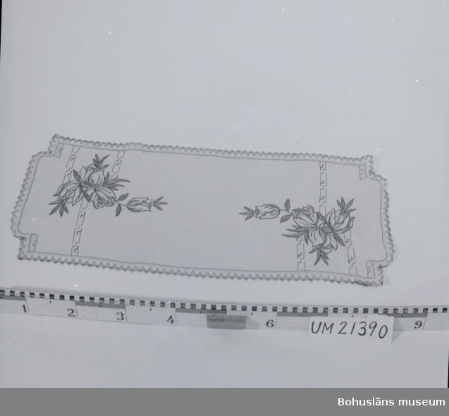 594 Landskap BOHUSLÄN  Troligen bomull, merciserat, moulinégarn (bomull). Beigefärgad botten. Broderade blombuketter och geometriskt motiv i ändarna. Kantad med spets i svart och beige.  UMFF 16:11