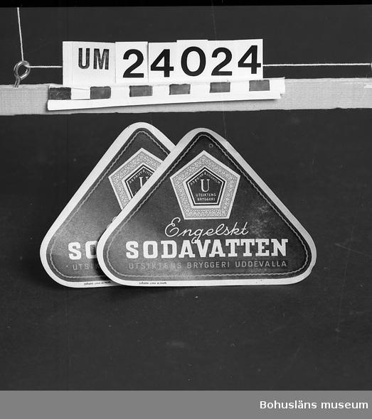 """Tresidig etikett för flaska, basen nedåt. Svart botten, vit och röd text och dekor: """"Engelskt Sodavatten. Utsiktens bryggeri i Uddevalla"""" samt dess varumärke. Oanvända.  Bryggeriet låg ungefär mellan Uddevalla gamla lasarett och Uddevalla - Vänersborg - Herrljungabanan. Var uppköpt under tiden efter andra världskriget av AB Pripp  & Lyckholm. Företaget grundades 1854, nedlades och revs 1961."""
