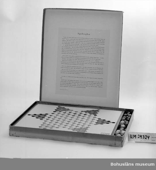 """Spelplan (av papp) och kulor (av trä) ligger i en papplåda. Lådan är blå och på locket är ett ljust fält påklistrat med svart text: """"Kines-schack. Ett mycket roligt spel"""". I locket finns ett rosa blad med spelregler. Undertill står det tryckt """"AG 531""""."""