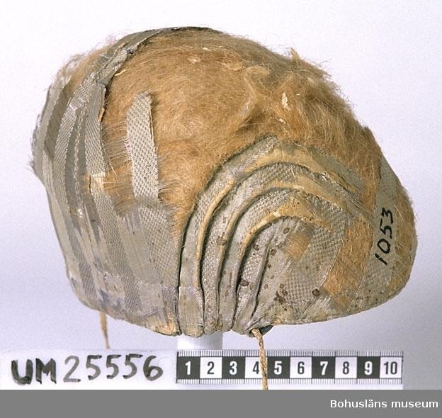 """Mössan har styv stomme av papp. Yttertyget är av ljusblått enfärgat siden, randmönstrat med ca 1,5 cm breda ränder i omväxlande satin och annan bindning. Av yttertyget återstår dock bara delar. Uppe på kullen och fram på sidostyckena är det helt bortslitet. Där ligger mellanlagret av linblånor i dagen. Fodertyg av kattun (bomullstyg med mönstertryck). Större delen av fodret är mönstrat med ljusblå stiliserade blommor utan stjälkar och ljusblå små prickar på mörkblå botten. En mindre bit, med smalrandig botten i vitt och ljusblått med mörkblå blomma, är inskarvad fram på höger mösshalva. Det huvudsakliga tyget är möjligen en typ av s.k. blåtryck, en sorts reservagetryck där mönsterpartierna trycks med en """"gröt"""" av okänd sammansättning som gör att de inte tar åt sig färg, beskriven i Rune Bondjers artikel """"Tygtryckning i Dalarna"""". (Se litt.listan) Mössan har snibb fram i pannan och fem svängda veck bak i varje sida. Dragband bak av brickvävt band. Ingen kanal för dragband på insidan. Bandet ligger istället under yttertyget mitt bak och ändarna av bandet sticker ut mellan ytter- och fodertyg vid yttersta vecken. Mössan är i mycket dåligt skick. De rester av yttertyget som finns är gulnat och bak på vänster sida fullt av små fläckar. Fodertyget är smutsigt. Även linblånorna är bortslitna på höger sidoflik. Mössans form liknar de bindmössor som finns i Folkdräkter och bygdedräkter i hela Sverige av Arnö-Berg, Inga, sid. 213. De är från Sorunda i Sörmland, s.k. Stockholmsmössor. Deras stommar är troligen tillverkade i stort antal i någon verkstad i Stockholm kring mitten av 1800-talet. Svängda veck finns på mössor med hård pappstomme som är av ganska sent datum. (Uppgiftslämnare angående Sorundamössorna: Ulla Centergran, fil. dr. i etnologi, dräktforskare) Tillverkningstid och användningstid är osäker men med anledning av ovanstående uppgifter är datering av den här mössan snävt gjord. Ägarens make var kusk på Morlanda säteri. De var bosatta på Kårehogen nära Morlanda kyr"""