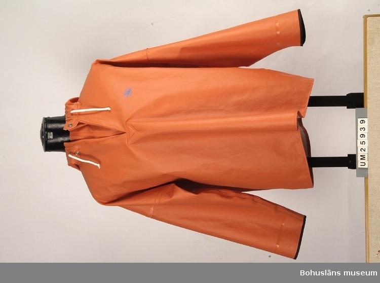"""Föremålet visas i basutställningen Kustland , Bohusläns museum, Uddevalla.  410 Mått  ÄL 52 CM Orangefärgad jacka, halsknäppning, huva. Tillhörande märkesetikett med produktionsuppgifter och skötselråd. Modellnamn: """"Brigg Slipover"""". På vänstra sida bröstet i blått tryck ett segelfartyg och """"Brigg"""". Sammanhör med byxor UM25938, se detta nr ang tillverkning.  Historik om Grundéns se UM25938."""