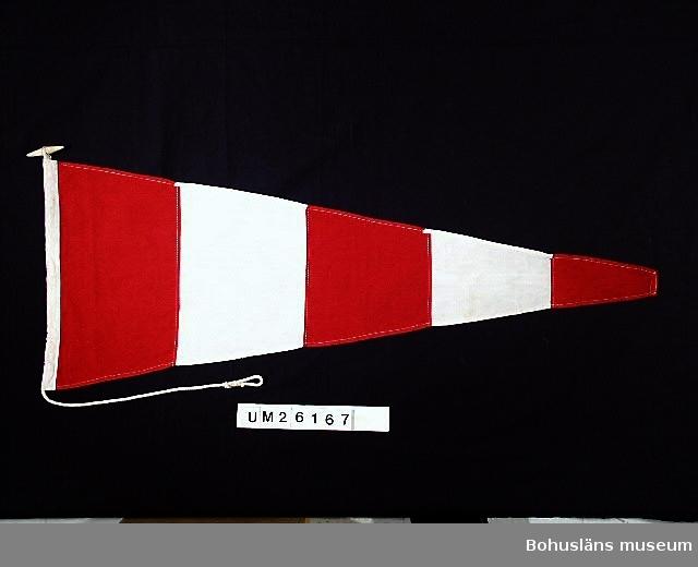 Vimpel med fem horisontella fält, varannat rött, varannat vitt. Rött innerst och ytterst. Kodvimpel (svansvimpel). Ena vimpeln av två något längre.  Användning se UM026139  Personuppgifter se UM026024