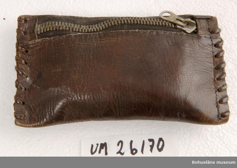 """Föremålet visas i basutställningen Kustland, Bohusläns museum, Uddevalla.  Funktion: Tobaksförvaring. Rektangulär pung, i ändarna hopsydd med läderremsa. Upptill isydd dragkedja. Innehåller tobak och tobaksfläta och litet paket cigarettpapper. Den innehåller även handskriven lapp med datum """"Den 12 april 1939"""". Denna dag beslöt sig Gösta Svedung för att inte röka vilket han höll livet ut.  Personuppgifter; se UM026024  Gösta Svedung var anställd vid Rederi AB Bohuslänska Kusten och förde befäl, framför allt på ångaren """"Göteborg"""" på traden Göteborg - Oslo. När detta rederi upphörde i början av 1950-talet övergick Gösta Svedung till Göta Kanalbolaget där han förde kanalbåtar mellam Göteborg och Stockholm. Gösta Svedung förlovade sig 1929 och gifte sig 18 oktober 1930 med Alice Grundberg. De förvärvade och bosatte sig i fastigheten Hedegatan 22 i Uddevalla, på vilken adress de var bosatta livet ut. De hade två döttrar."""