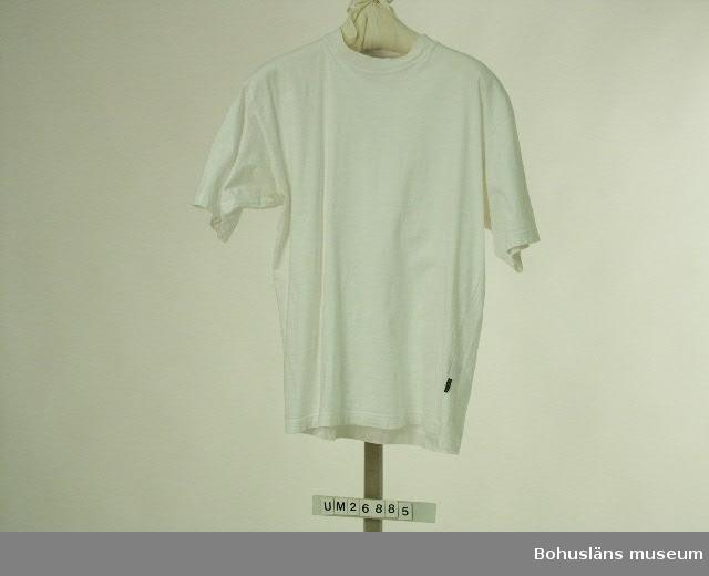 """410 Mått/Vikt ÄL 17,5 CM Kortärmad tröja utan krage. Av vit trikå. Rundringad hals kantad med vit mudd. Invändigt i nacken förstärkning med vit trikåremsa. Nertill och runt ärmarna fållat med tvillingnål. Snedvridna sidsömmar (ett fabrikationsfel som är vanligt på t-shirts). I sidsömmmen på vän- ster sida finns en mycket mörkt blå tygetikett med beige invävda bokstäver: """"L.O.G.G."""". Invändigt mitt bak i nacken finns två tygetiketter i samma färger, en liten märkt """"M"""" (storleksmärkning) och en större märkt: """"L.O.G.G. Label Of Graded Goods"""". Tvättrådsetikett invändigt i vänster sidsöm.  L.O.G.G. är ett varumärke som säljs på Hennes och Mauritz (H&M) i slutet av 1990-talet. Anders vet inte när den här t-shirten är köpt. Anders har ofta t-shirt under kläderna,  inte bara under segelsemestern utan även till vardags.  Insamlad i samband med SAMDOK-dokumentation av båtturism.  För mer uppgifter om brukaren och dokumentationen se UM26869."""